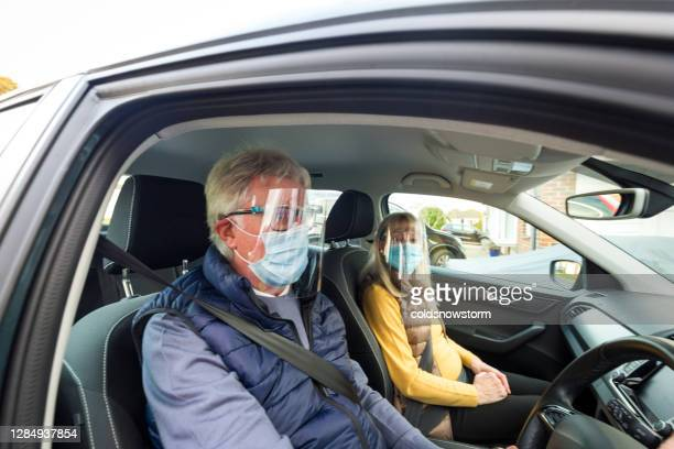senior couple in car wearing face shield and protective mask - fragility stock pictures, royalty-free photos & images