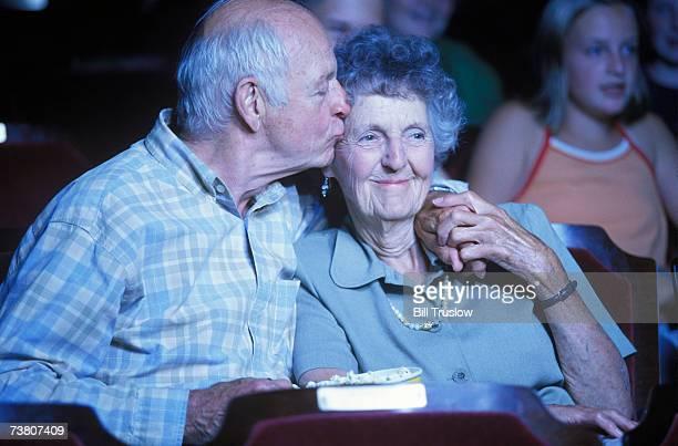 Senior couple in cinema, man kissing woman's forehead
