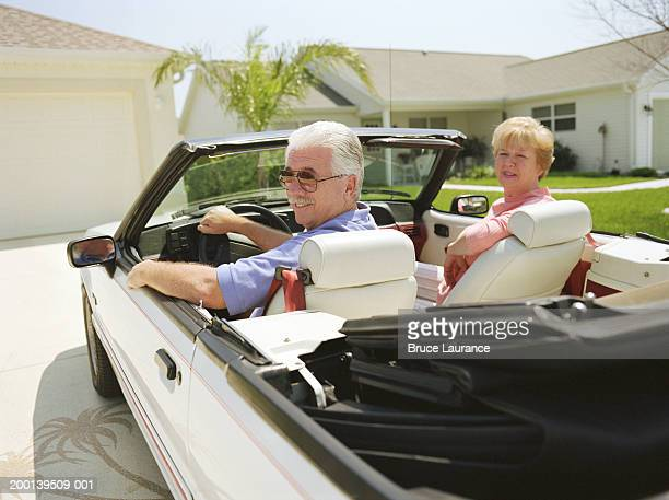 Senior couple in convertible car backing out of driveway