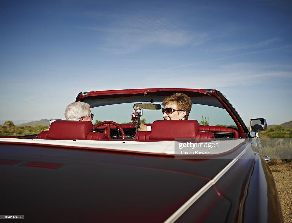 Senior couple in convertible wife taking photo : Stock Photo