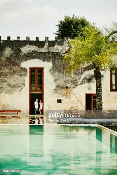Senior couple in discussion while standing in doorway of tropical luxury resort