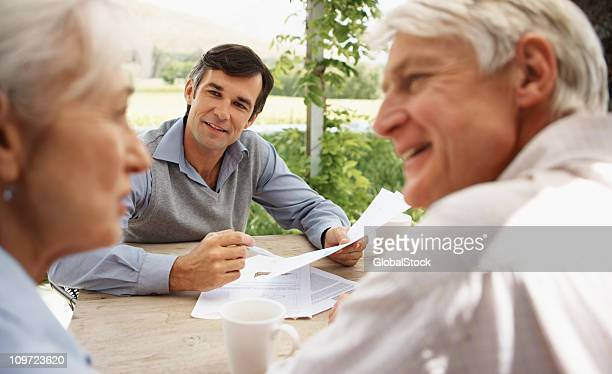Senior couple in discussion with a real estate agent