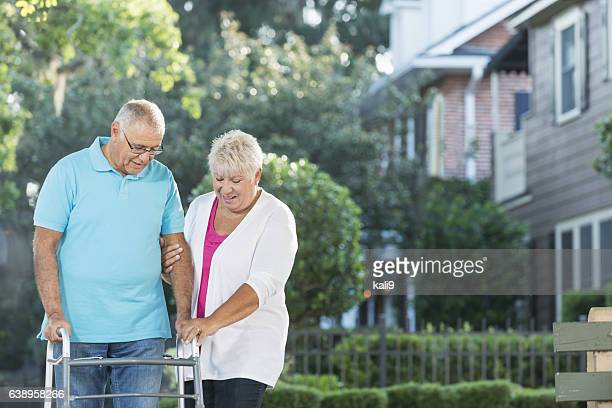 Senior couple in front of house, man using walker