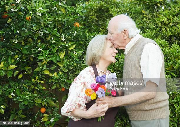 Senior couple in garden kissing, woman holding flowers