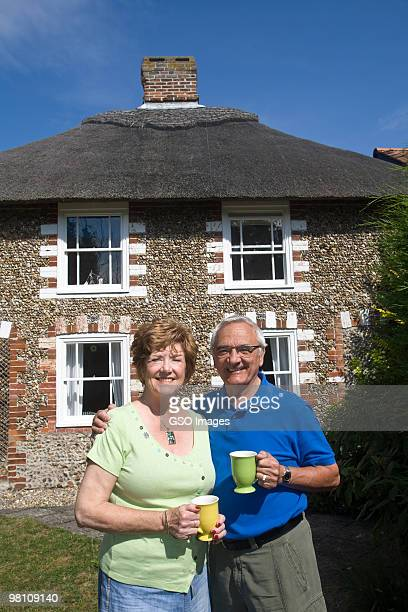 senior couple in garden of country cottage - in front of stock pictures, royalty-free photos & images