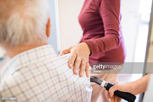 senior couple in hospital - hand on shoulder stock pictures, royalty-free photos & images