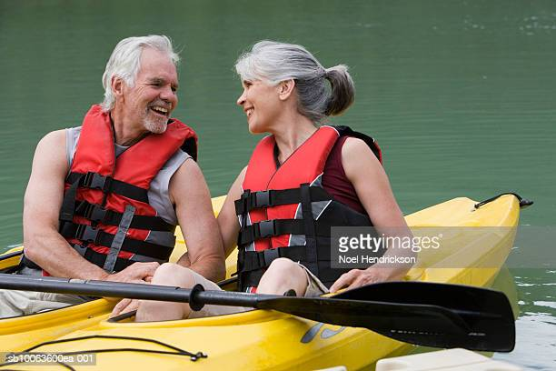 Senior couple in kayaks, looking in eyes and laughing