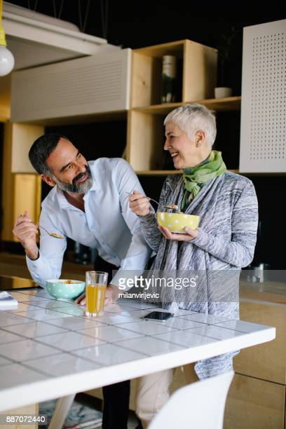 Senior couple in kitchen having breakfast and talking