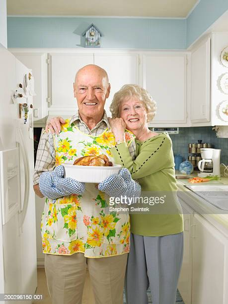Senior couple in kitchen, man holding dish with roasted chicken