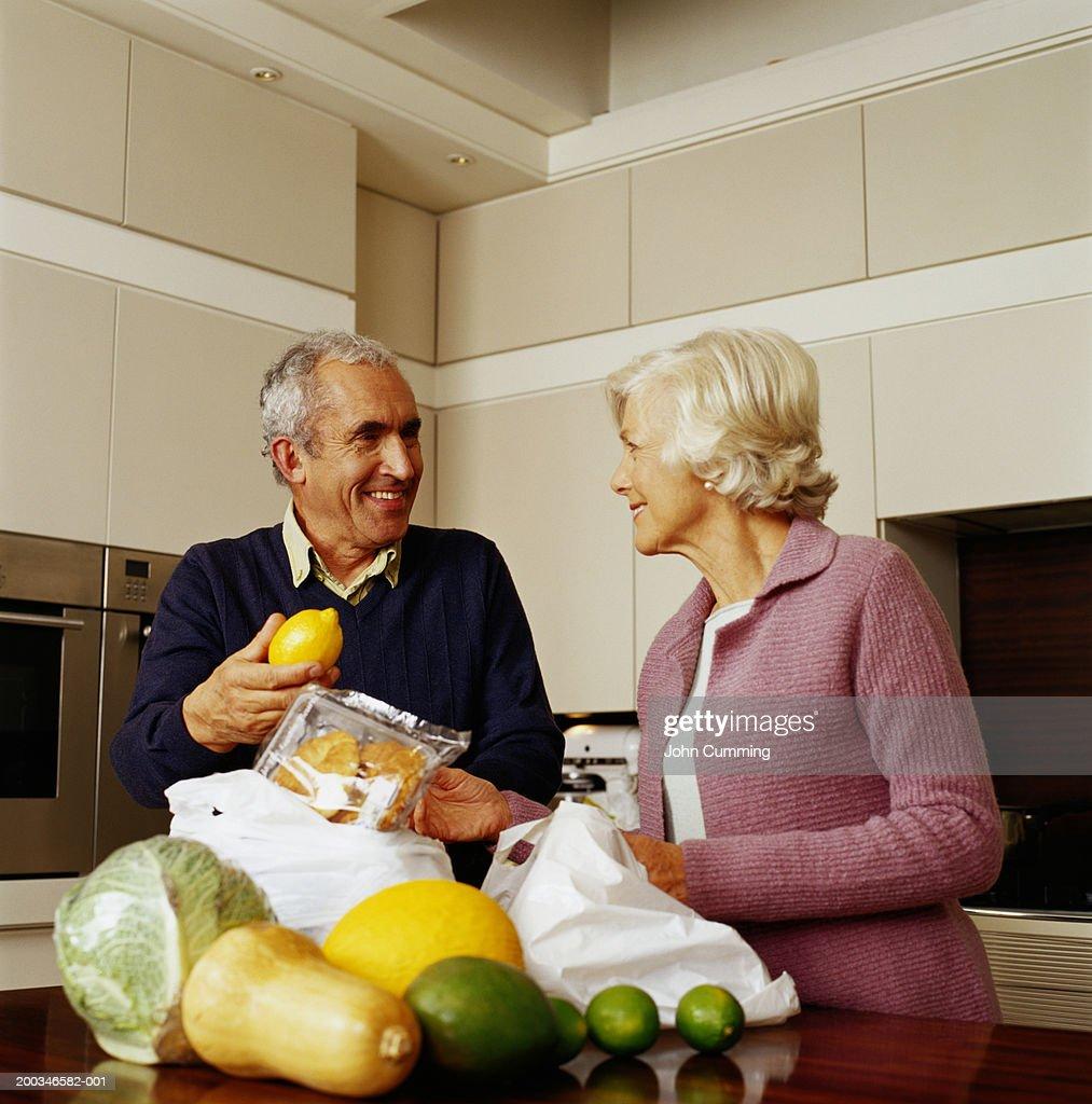 Senior Couple In Kitchen, Man Holding Lemon, Smiling : Stock Photo