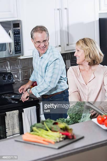 Senior couple in kitchen preparing dinner together
