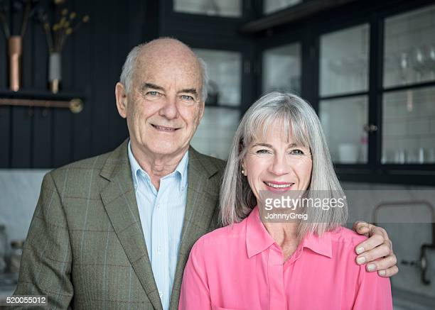 Senior couple in kitchen smiling, man's hand on woman's shoulder