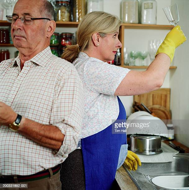 senior couple in kitchen, woman holding up wine glass to light - couples showering stock pictures, royalty-free photos & images