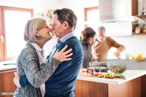 Senior couple in love hugging in the kitchen at home with friends cooking dinner in the background.