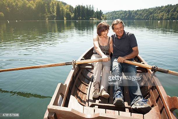 senior couple in love in a boat on a lake - rowing boat stock pictures, royalty-free photos & images