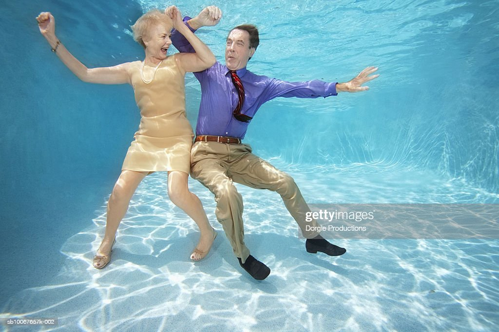 Senior Couple In Normal Clothes Dancing Underwater Stock Photo