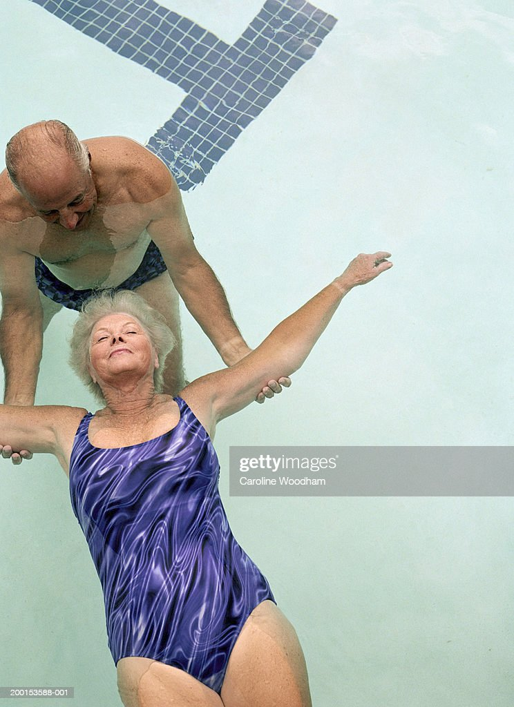 Senior couple in pool man helping woman float on back for Pool man show