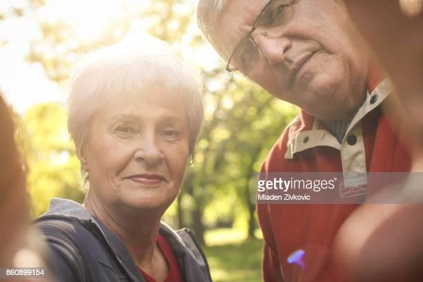 Älteres Paar in Sportbekleidung eine Kamera zusammenzuhalten.