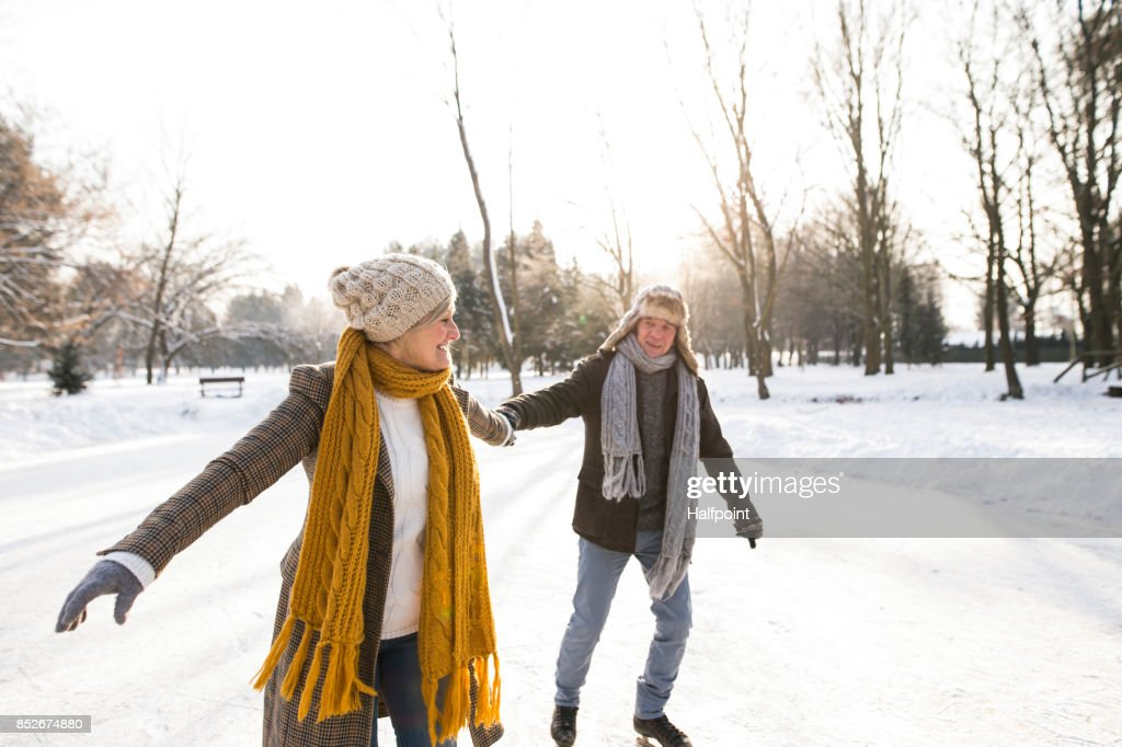 Senior couple in sunny winter nature ice skating. : Stock Photo