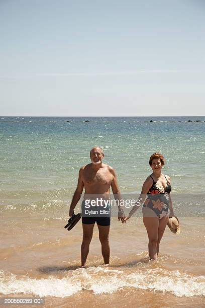 Senior couple in swimming costumes standing in surf, smiling, portrait