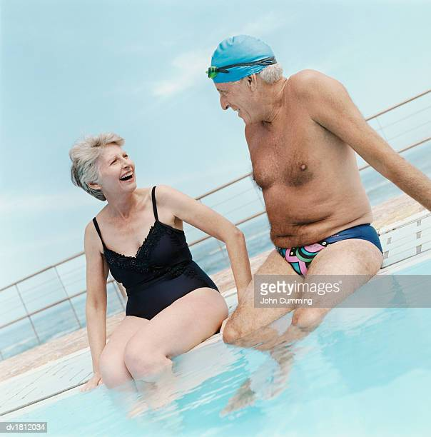 Senior Couple in Swimwear Sit at the Side of the Pool, Talking and Laughing