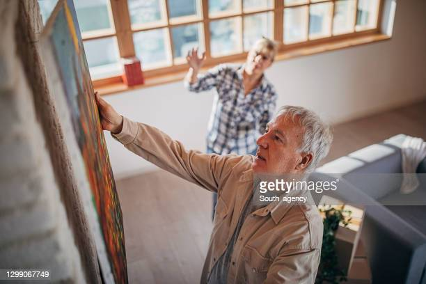 senior couple in their new home hanging a painting together - hanging stock pictures, royalty-free photos & images