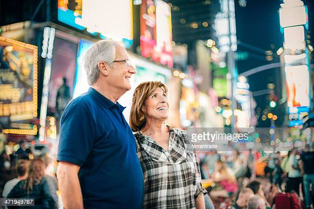 senior couple in times square new york - broadway manhattan stock photos and pictures