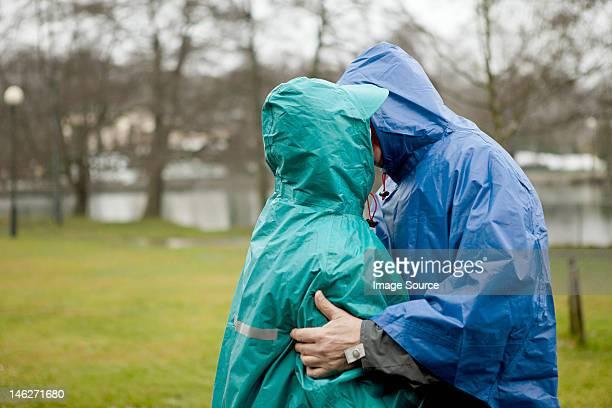 Senior couple in waterproof clothing kissing in park
