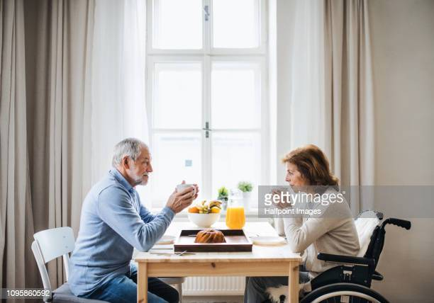 a senior couple in wheelchair sitting at the table at home, eating and drinking tea or coffee. - husband stock pictures, royalty-free photos & images