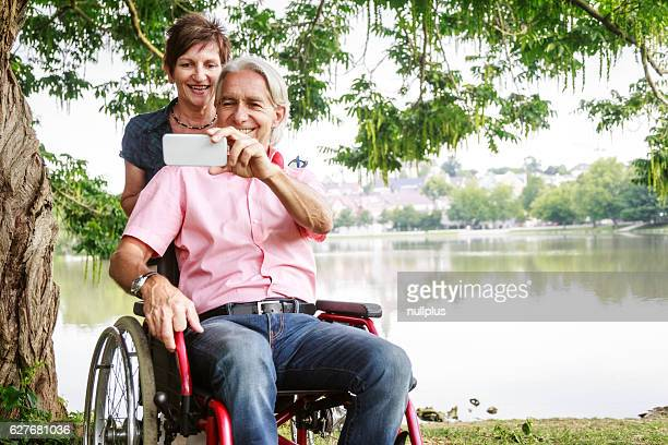 Senior couple in wheelchair, taking selfies