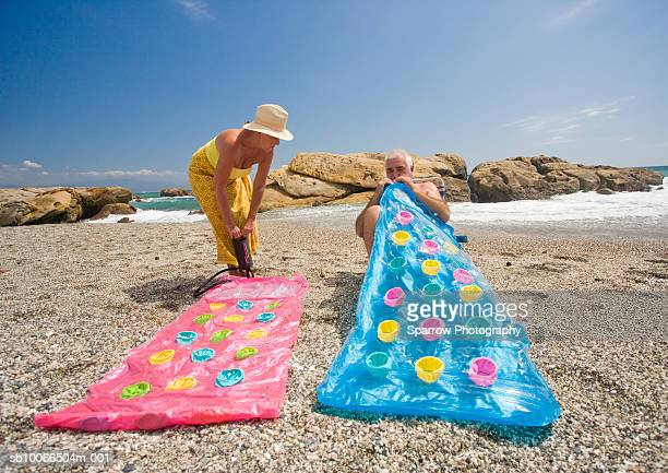 Senior couple inflating airbeds on beach
