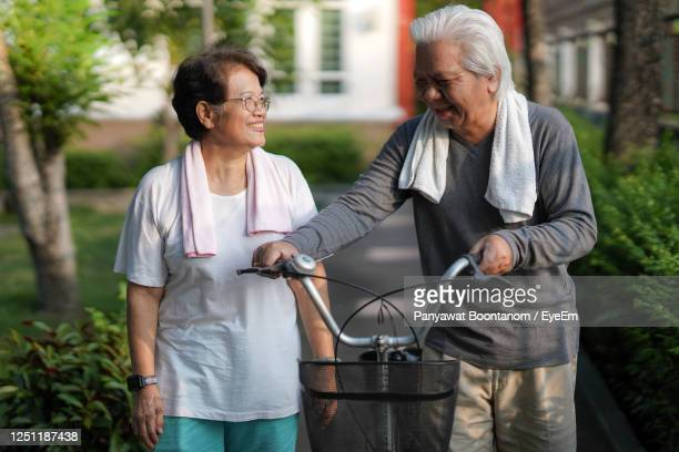 "a senior couple is happily riding their bicycles in the park in the morning. - ""panyawat boontanom"" stockfoto's en -beelden"
