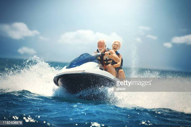 senior couple jet skiing. - jet ski stock pictures, royalty-free photos & images