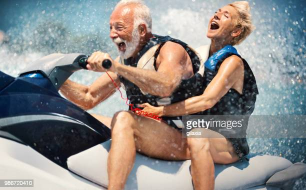 senior couple jet skiing. - boat stock pictures, royalty-free photos & images