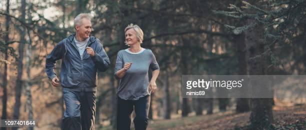 senior pareja corriendo en un bosque - sporting term fotografías e imágenes de stock