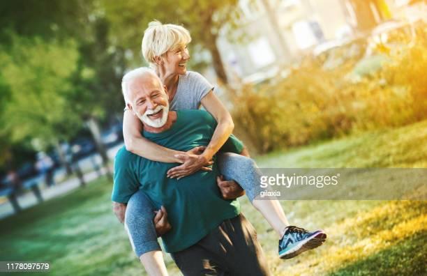 senior-paar joggen in einem wald. - bewegung stock-fotos und bilder