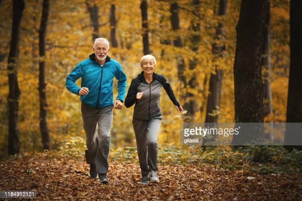 pareja mayor corriendo en un bosque. - sporting term fotografías e imágenes de stock