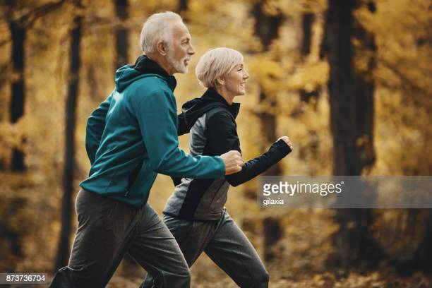 senior couple jogging in a forest. - exercising stock pictures, royalty-free photos & images