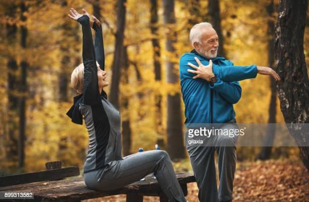 senior pareja a correr por un bosque. - chándal fotografías e imágenes de stock