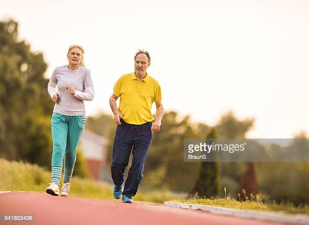 Senior couple jogging on a running track outdoors.
