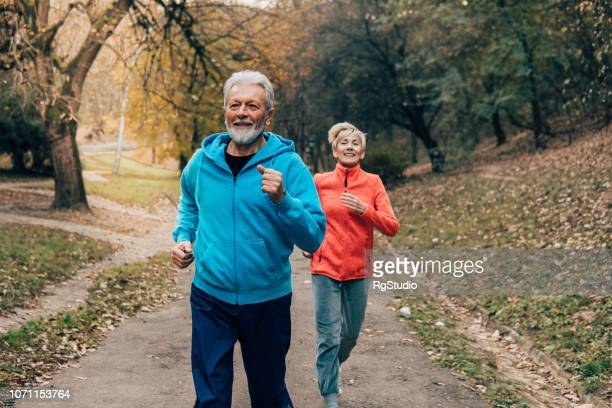 senior couple jogging outdoors - termine sportivo foto e immagini stock