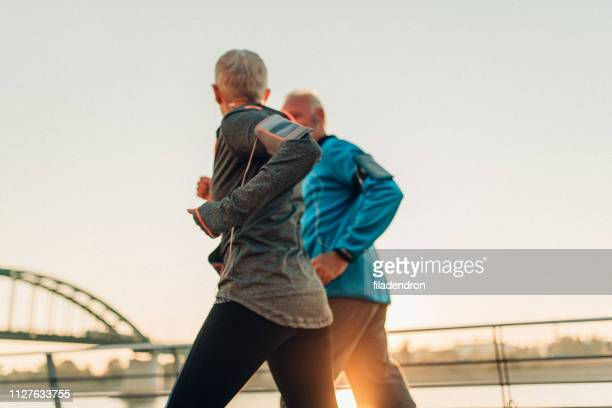 senior couple jogging together - relaxation exercise stock pictures, royalty-free photos & images