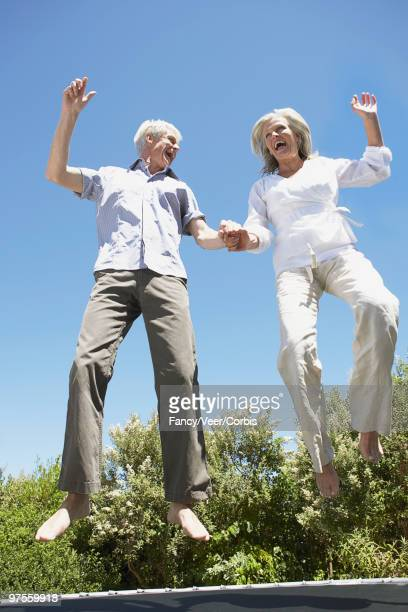 Senior couple jumping on trampoline