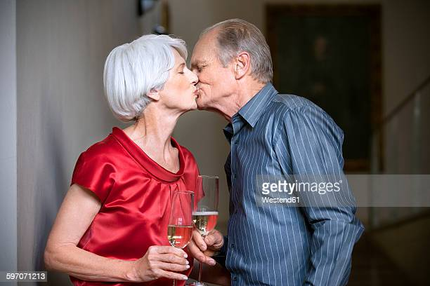 Senior couple kissing and clinking glasses
