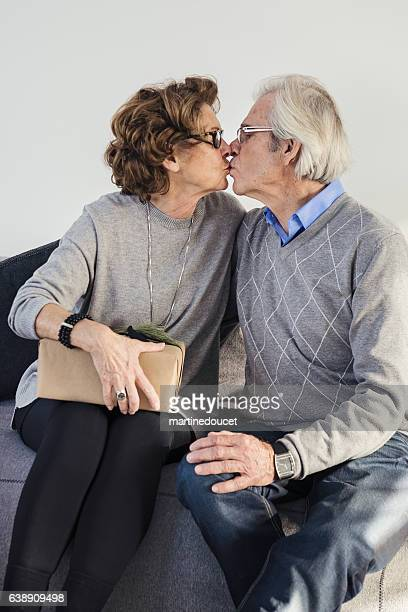 "senior couple kissing before opening a gift. - ""martine doucet"" or martinedoucet stock-fotos und bilder"