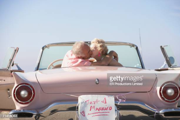 senior couple kissing in pink convertible with just married sign - newlywed stock pictures, royalty-free photos & images
