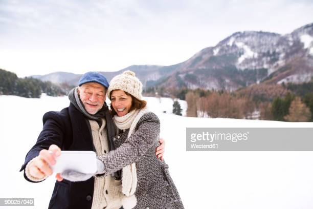 Senior couple kissing taking selfie with cell phone in winter landscape