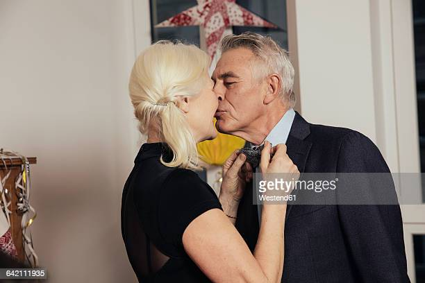 Senior couple kissing while fastening bow tie for New Year's Eve party