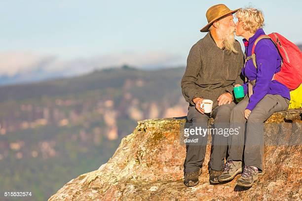 Senior Couple Kissing While Taking a Break from Bushwalking
