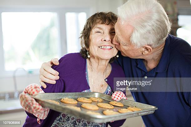 Senior couple kissing with home baked cookies